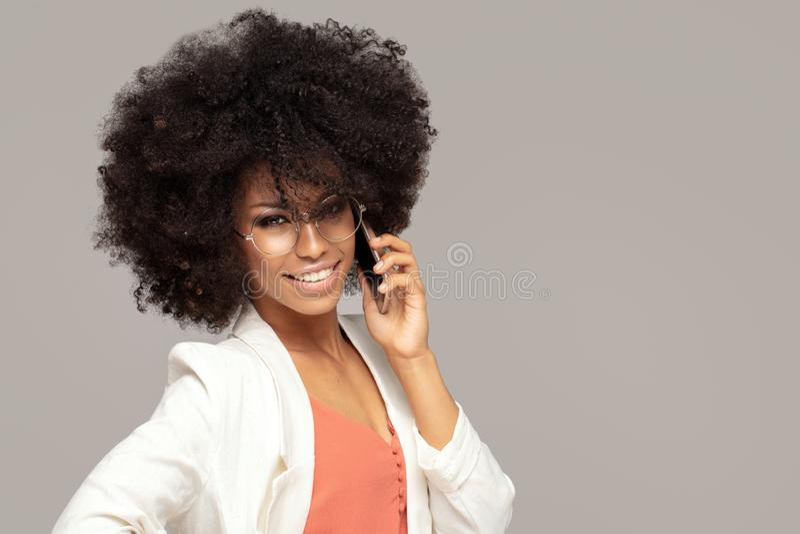 Schöne Afrofrau, die durch Handy spricht stockfoto