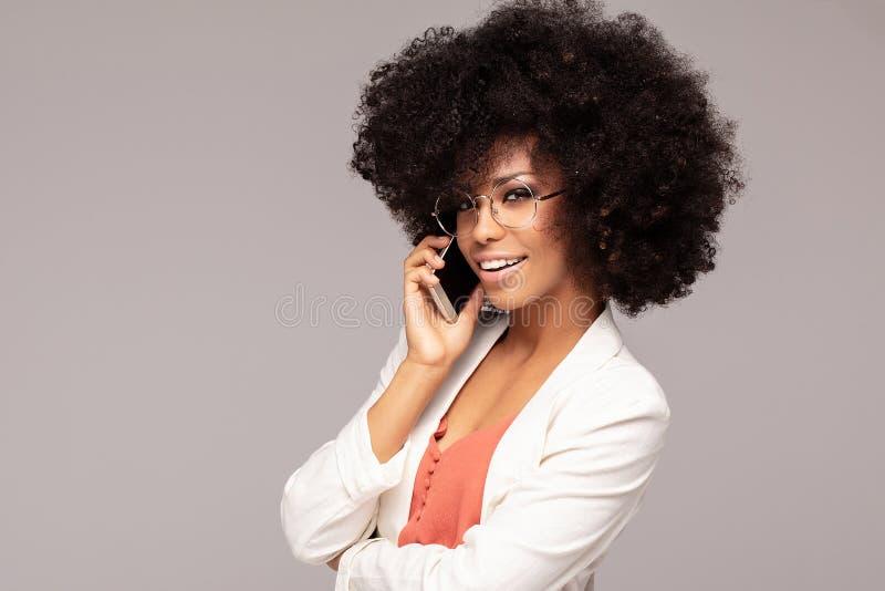 Schöne Afrofrau, die durch Handy spricht stockbilder