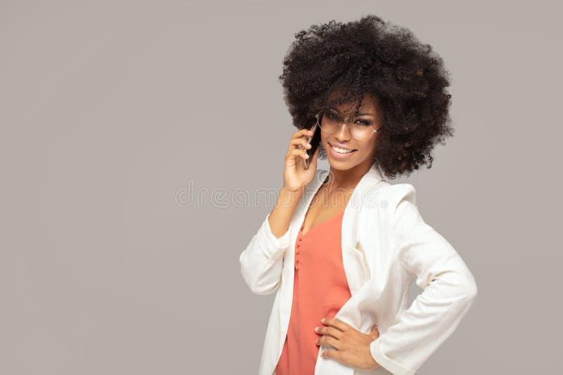 Schöne Afrofrau, die durch Handy spricht stockfotografie