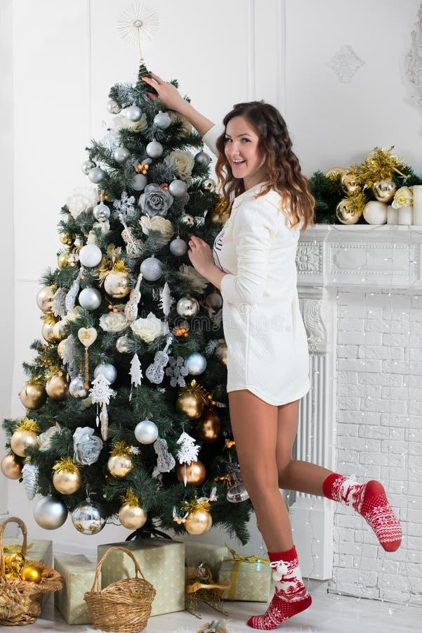 Schöne aktive Frau verziert Weihnachtsbaum lizenzfreies stockbild