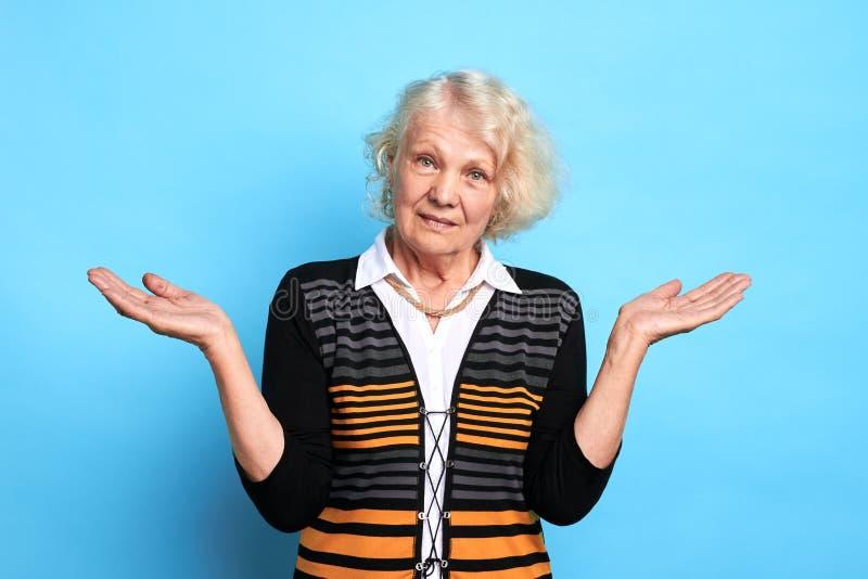 Schöne alte Frau in der stilvollen Kleidung zuckt Schultern lizenzfreie stockfotos