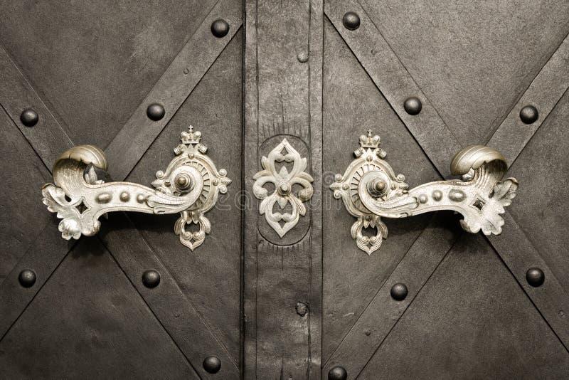 Schöne alte Türgriffe und Dekoration machten vom Silber auf einer dunklen Tür stockfoto