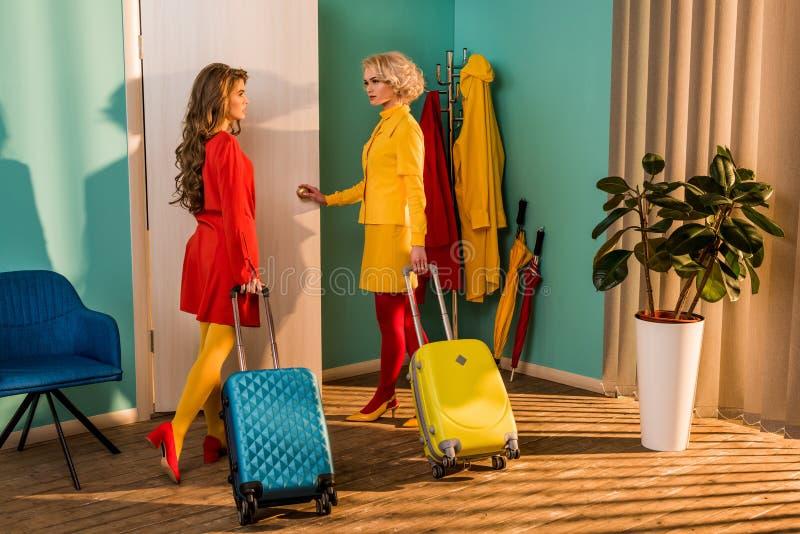 schöne altmodische Mädchen in den bunten Kleidern mit Reisetaschen-Öffnungstür lizenzfreie stockfotografie
