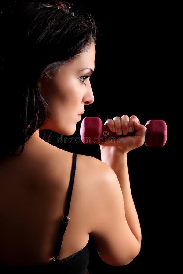 Schöne anhebende Eignunggewichte der jungen Frau stockfotografie