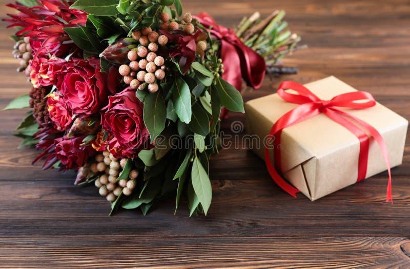 Schöne Anordnung der frischen Blume für rote Rosen und Geschenkbox lizenzfreie stockfotografie