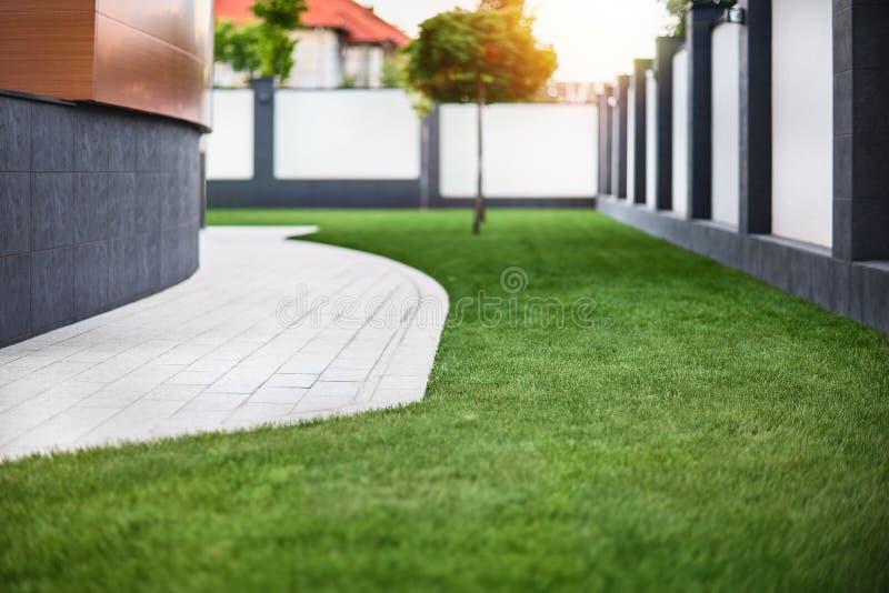 Schöne Ansicht über netten Hinterhof am sonnigen Tag, frischer Rasen des grünen Grases im Sonnenlicht, gestaltend im Garten, Schö stockfotografie