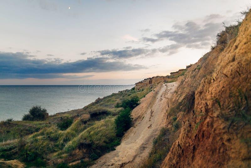 Schöne Ansicht der sandigen Klippe nahe Seestrand im Sonnenuntergang Landschaft der Strandklippe und der Wellen und des bewölkten stockfotografie