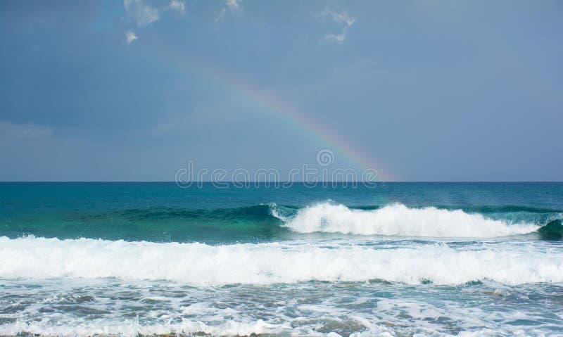 Schöne Ansicht des raibow über dem Meer und den Wellen, die auf dem Ufer bremsen lizenzfreies stockfoto