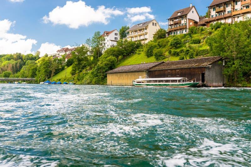 Schöne Ansicht des Rheins im Türkis, an der Quelle in der Schweiz, gerade hinter dem größten Wasserfall in Europa stockfotos