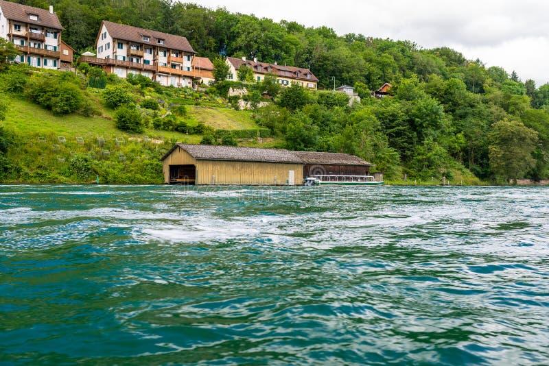 Schöne Ansicht des Rheins im Türkis, an der Quelle in der Schweiz, gerade hinter dem größten Wasserfall in Europa stockbild