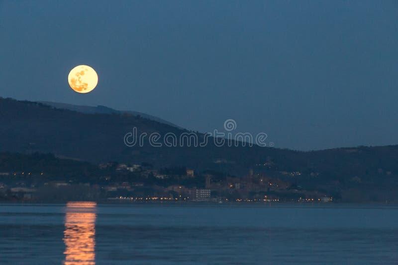 Schöne Ansicht des Vollmonds gerade über Passignano Umbrien, refle lizenzfreie stockbilder