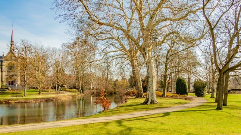 Schöne Ansicht eines Parks mit einem Teich, ein Weg, Bäume und grünes Gras und eine Kirche im Hintergrund lizenzfreies stockbild