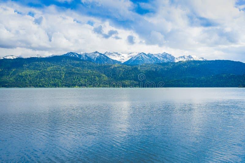 Schöne Ansicht von einem See zu den Bergen im Bayern teils bedeckt im Schnee stockbild