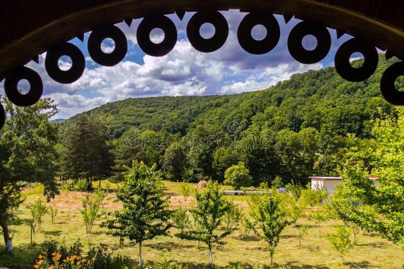 Schöne Ansicht von unterhalb des Überdachung Gazebo zum Garten mit jungen Bäumen und grünen Berghängen gegen stockfotografie