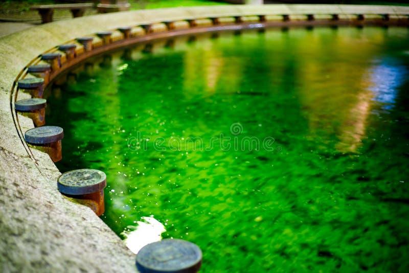 Schöne Ansicht zu einem grünen Wasserbrunnen mit alter Dekoration in einem italienischen Dorf nachts stockfotos