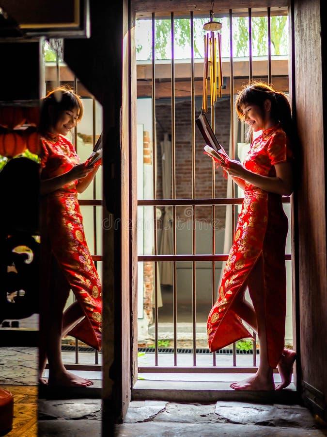 Schöne Asiatin in Cheongsam-Kleid, rotes chinesisches Kleid Sie steht vor dem Eingang, der chinesischen Innenraum hatte lizenzfreie stockfotografie