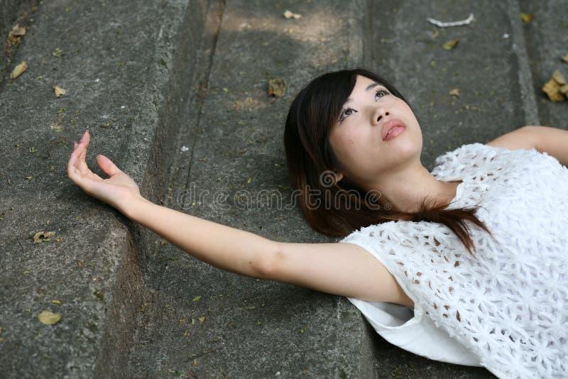 Schöne Asiatin, die auf Zementschritten liegt lizenzfreies stockbild