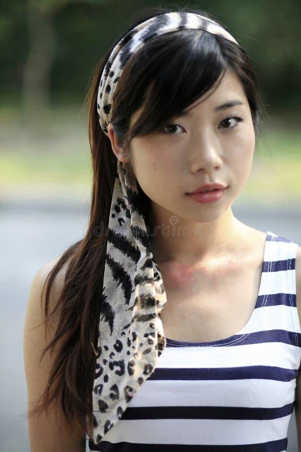 Schöne Asiatin, die den Zuschauer mit einem Kopftuch auf ihrem Kopf betrachtet stockbilder