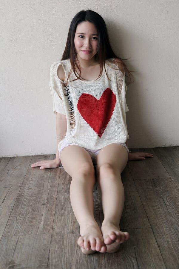 Schöne Asiatin, die mit ihren Beinen heraus ausgedehnt sitzt stockfoto