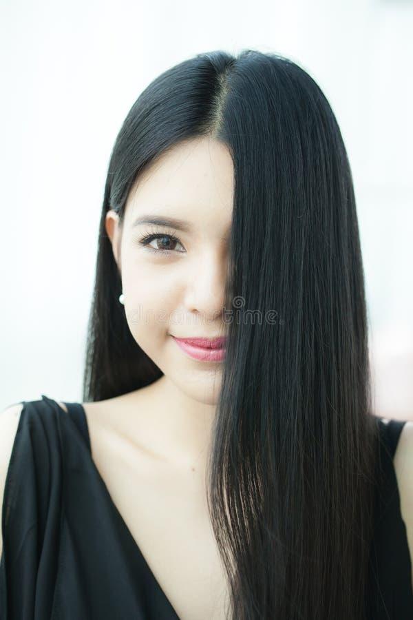 Schöne Asiatin mit dem geraden gesunden dunklen Haar - Haarpflege stockfoto