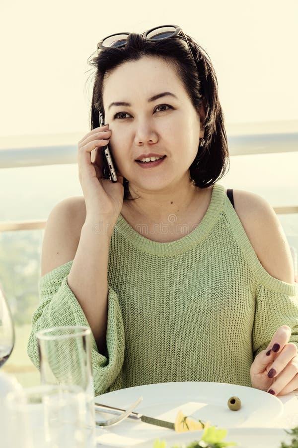 Schöne Asiatin mit einem Telefon in einem Restaurant stockfotografie