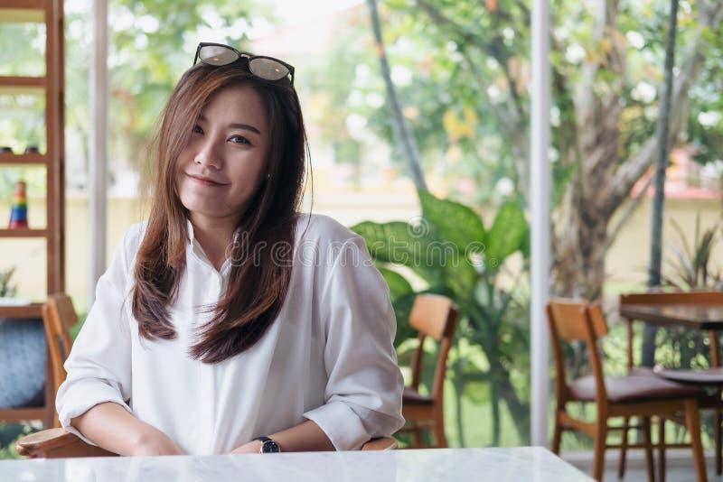 Schöne Asiatin mit smileygesicht und glaubendes gutes Sitzen im Café mit grünem Naturhintergrund lizenzfreie stockfotografie