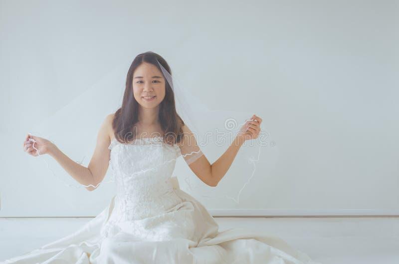 Schöne asiatische Brautfrau in den weißen Kleiderhänden, die Blume mit Gefühl glücklich und lustig halten stockfotografie