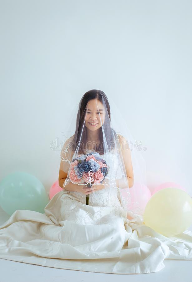 Schöne asiatische Brautfrau in den weißen Kleiderhänden, die Blume mit Gefühl glücklich und lustig halten stockbild