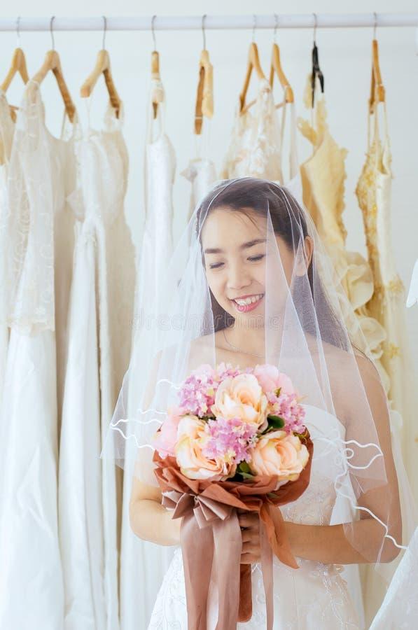 Schöne asiatische Brautfrau, die an Hand einen Blumenstrauß für die Heirat mit dem Fällen schüchterner, romantischer und sü lizenzfreie stockfotografie