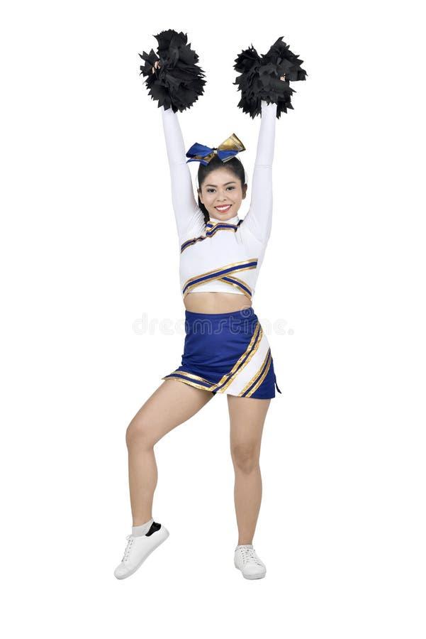 Schöne asiatische Cheerleader mit den Händen in der Luft mit Pom-poms stockfotos