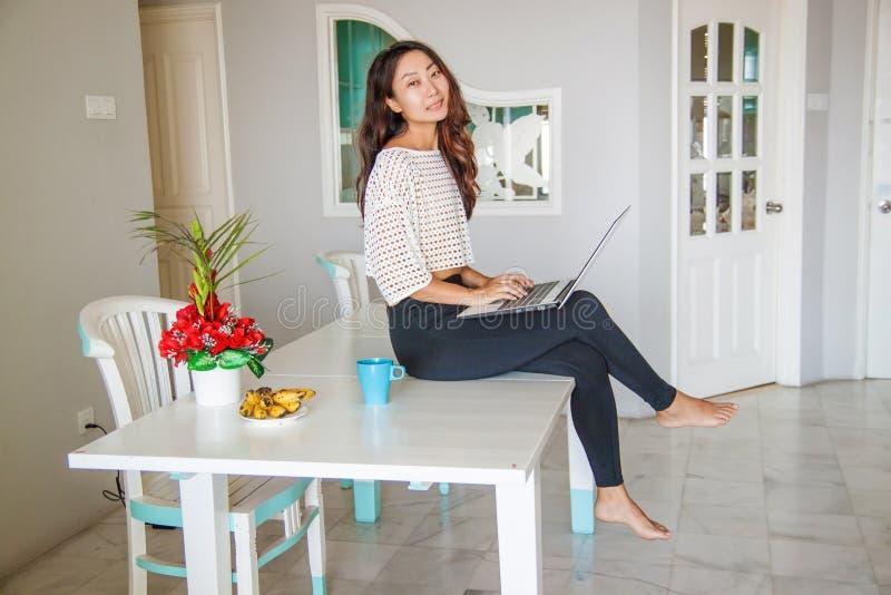 Schöne asiatische chinesische Frau, die Laptop-Computer verwendet lizenzfreie stockfotografie