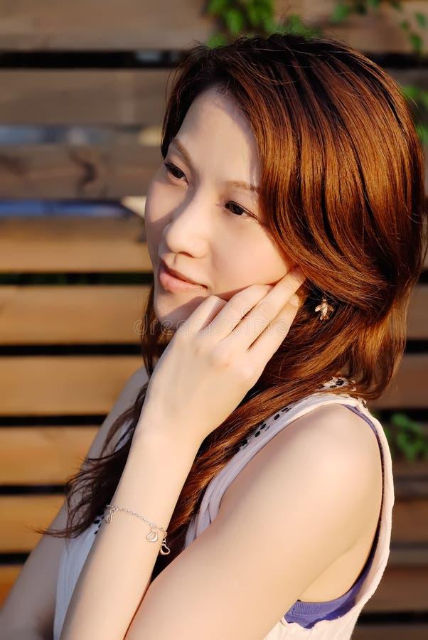 Schöne asiatische Dame mit der Sonnenuntergangleuchte stockbild