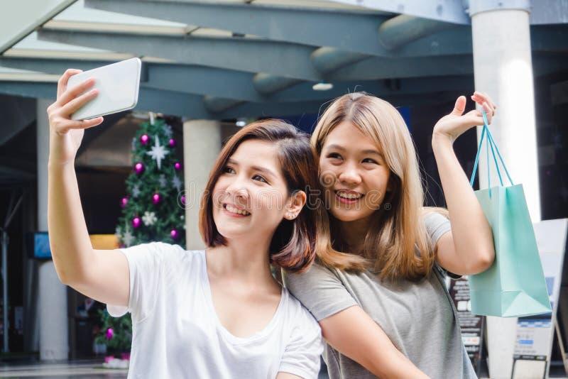 Schöne asiatische Einkaufstaschen unter Verwendung eines intelligenten Telefon selfie haltene, bei draußen stehen lächelnde Mädch lizenzfreie stockbilder