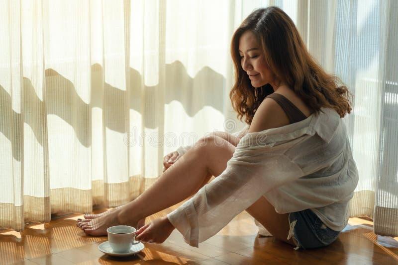 Schöne asiatische Frau, die eine Schale heißen Kaffee sitzt und ergreift, um auf dem Boden morgens zu trinken lizenzfreie stockbilder