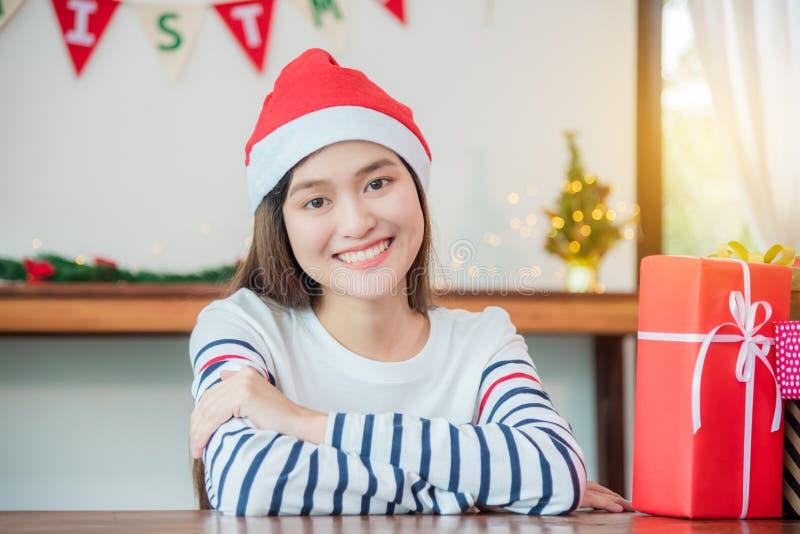 Schöne asiatische Frau, die Weihnachtsmann-Hut lächelt mit Chris trägt lizenzfreie stockbilder