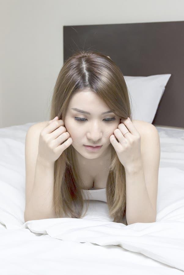 Schöne asiatische Frau im Bett lizenzfreie stockfotografie