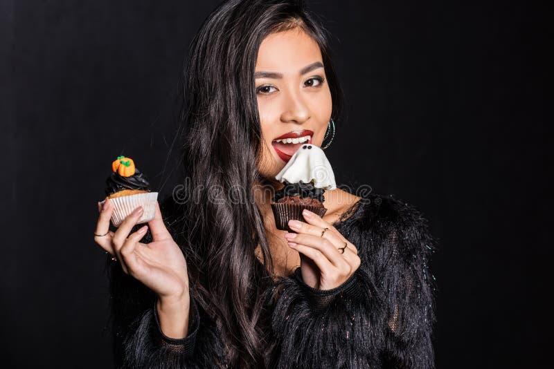 schöne asiatische Frau im Strauß versieht den Mantel mit Federn, der zwei kleine Kuchen in ihren Händen und in Schauen hält lizenzfreie stockfotos