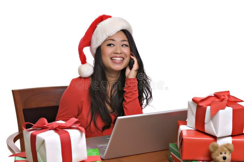 Schöne asiatische Frau kauft online für Weihnachten lizenzfreie stockbilder