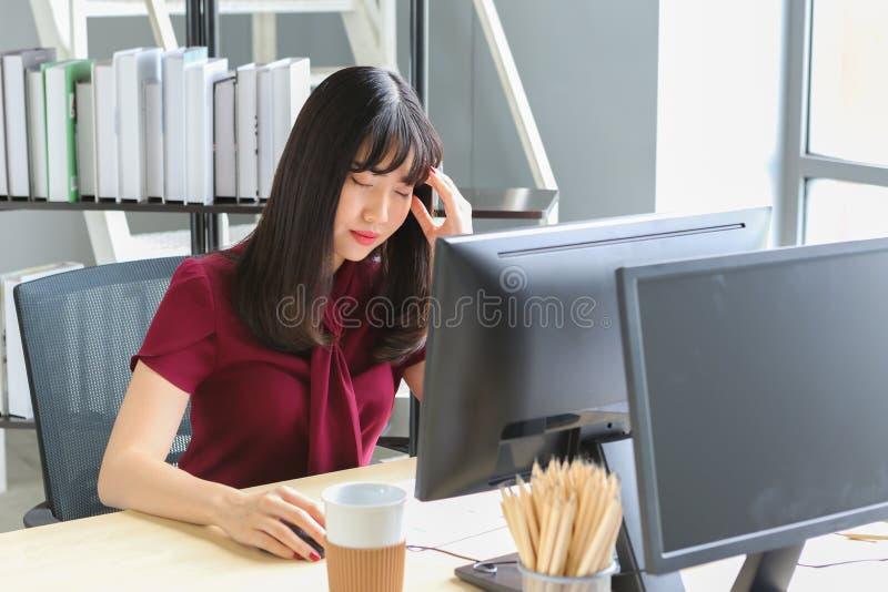 Schöne asiatische Frau mit den Kopfschmerzen, die Tempel beim Arbeits Computer auf Holztisch berühren lizenzfreie stockfotos