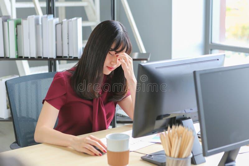 Schöne asiatische Frau mit den Kopfschmerzen, die zwischen den Augenbrauen beim Arbeits Computer auf Holztisch sich berühren lizenzfreie stockbilder