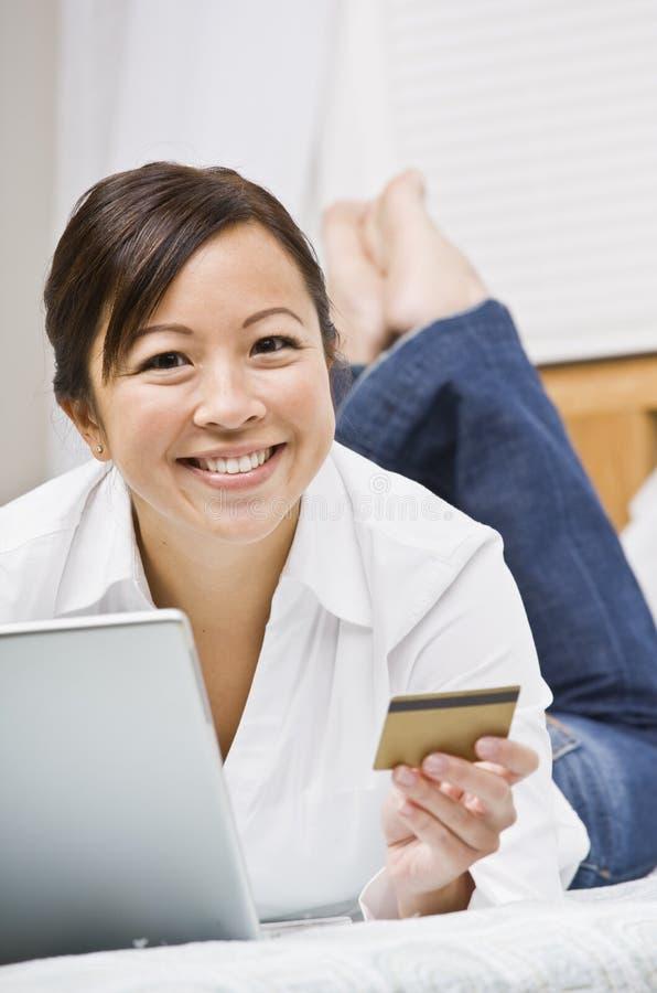 Schöne asiatische Frau mit Kreditkarte lizenzfreies stockfoto