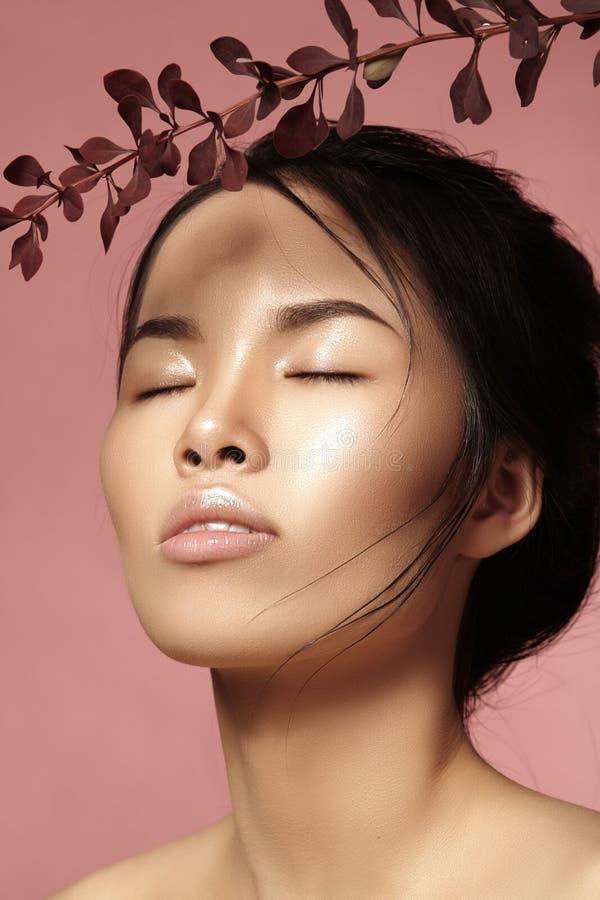 Schöne asiatische Frau mit neuem täglichem Make-up Vietnamesisches Schönheitsmädchen in der Badekur mit Grün treibt nahe Gesicht  lizenzfreie stockfotografie