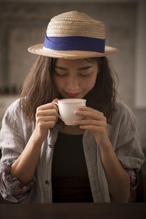 Schöne asiatische Frau und lächelndes Gesicht des heißen Kaffeetasseglückes stockfoto