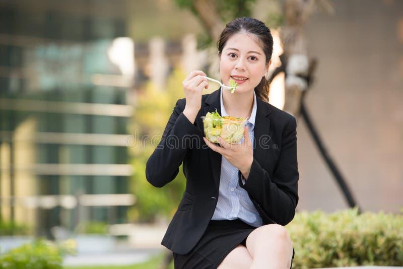 Schöne asiatische Geschäftsfrau, die Salat auf Parkbank isst stockbild