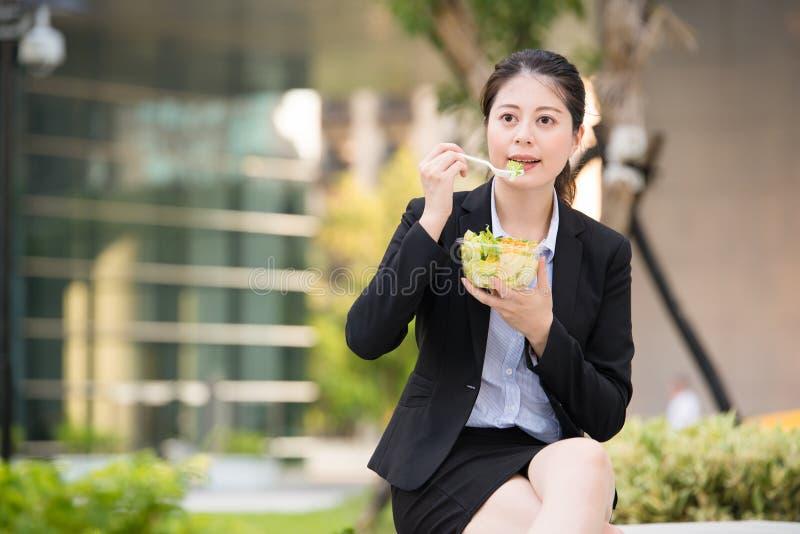 Schöne asiatische Geschäftsfrau, die Salat auf Parkbank isst lizenzfreies stockbild
