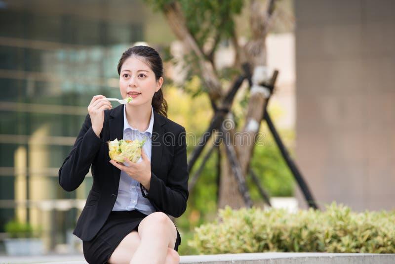Schöne asiatische Geschäftsfrau, die Salat auf Parkbank isst stockfoto