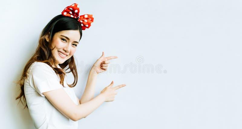 Schöne asiatische Hochschul- oder Studentfrau, die das lustige Bogenstirnband, zeigend auf Kopienraum auf whiteboard Hintergrund  stockbilder