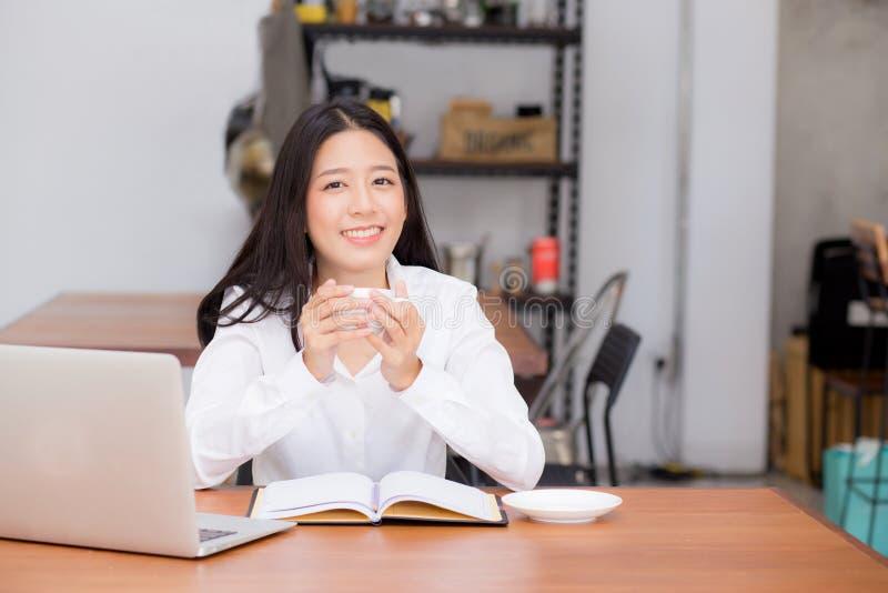 Schöne asiatische junge Frau, die online an dem Laptop und Getränkkaffee sitzen an der Kaffeestube arbeitet lizenzfreies stockbild
