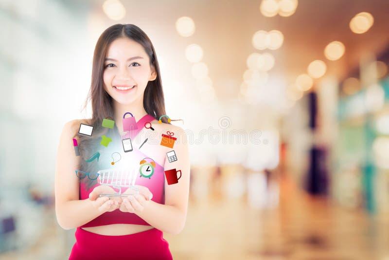 Schöne asiatische junge Frau im roten Kleid, das Warenkorb hält lizenzfreies stockbild
