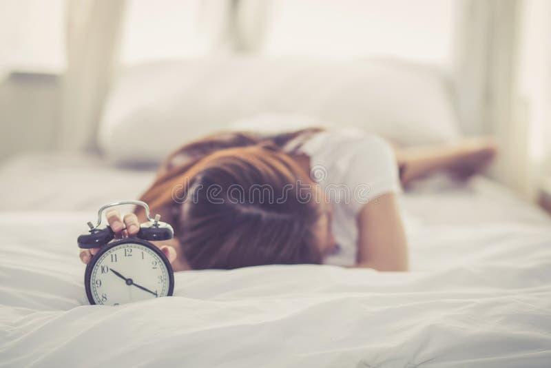 Schöne asiatische junge Frau stellen Wecker am guten Morgen ab stockfoto
